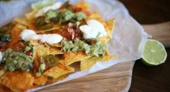 Cheesy nachos with guac, tomato salsa and sour cream