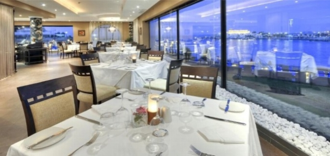 White linen table cloths and surrounding views of St George's Bay makes dining at Grill 3301 a breathtaking experience