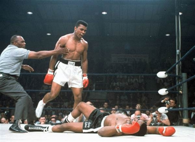 Muhammad Ali is held back by referee Joe Walcott, left, after Ali knocked out challenger Sonny Liston in the first round of their title fight in Lewiston, Maine on May 25, 1965