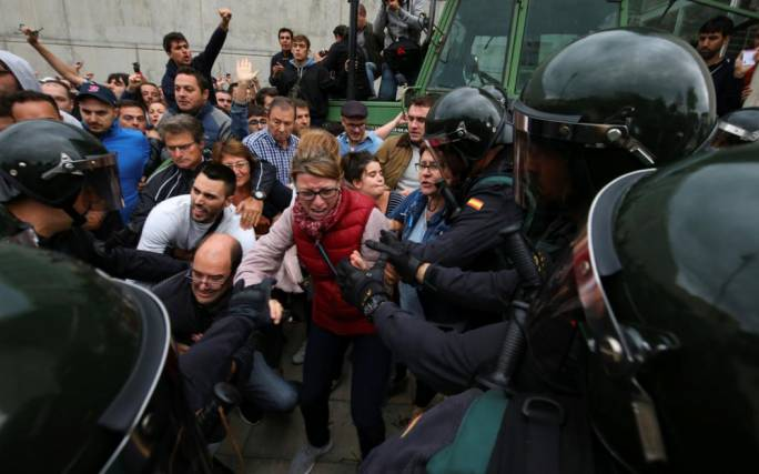 Spanish Civil Guard officer pushes a man outside a polling station for the banned independence referendum in Sant Julia de Ramis, Spain on 1 October (Photo: the National)