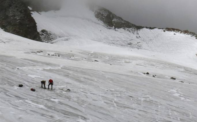 Police investigate the site where the body of a German hiker was found in the Valais canton near Saas-Fee, Switzerland