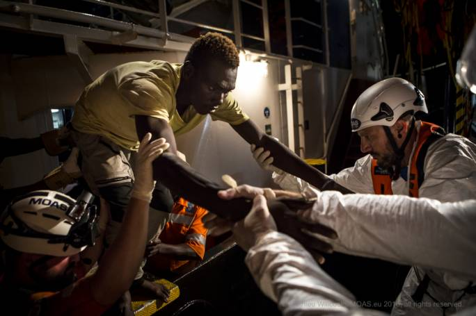 A migrant taken aboard a rescue vessel after daring his life at sea