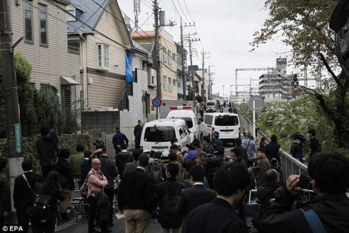 Police investigators guard an apartment building (centre, blue sheet) as members of the media crowd around in Zama (Photo: DailyMail)