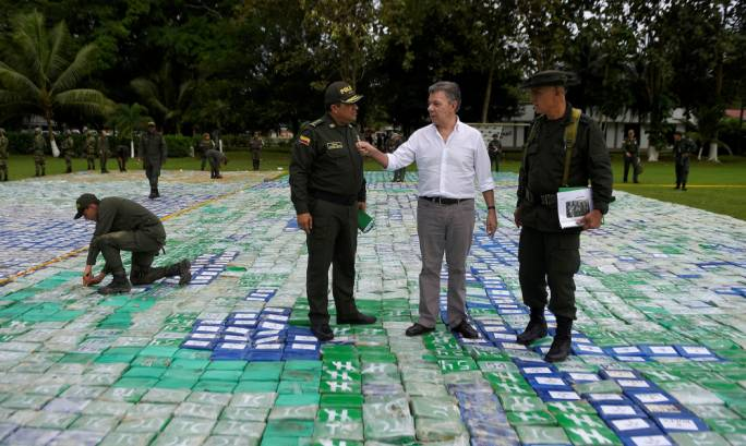 Colombian police and soldiers guard more than 12 tons of seized cocaine in Apartado, Colombia (Photo: the Guardian)
