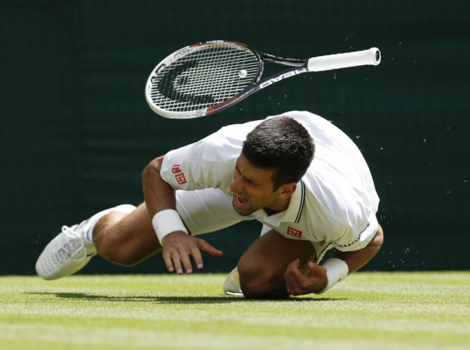 Novak Djokovic of Serbia takes a fall as he plays Gilles Simon of France in their third round match during the Wimbledon Championships. Photo by EPA/VALDRIN XHEMAJ