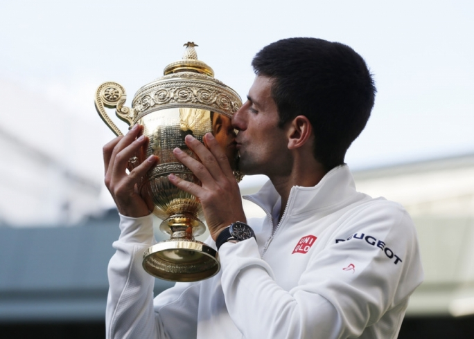 Novak Djokovic of Serbia kisses the championship trophy following his win over Roger Federer of Switzerland in the men's singles final of the Wimbledon Championships at the All England Lawn Tennis Club, in London, Britain, 06 July 2014. Photo by EPA/SANG TAN / POOL