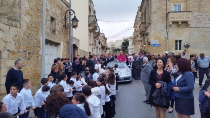 Fr Sultana on a Porsche Boxter being pulled by a group of children