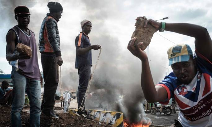 Opposition supporters hold up bricks as they block streets and burn tyres during a protest on Wednesday in Kisumu, where demonstrations are now prohibited. (Photo: Yasuyoshi Chiba/AFP)