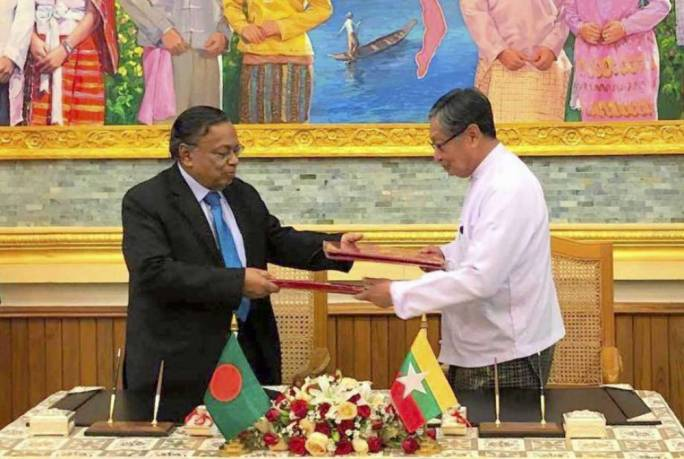 Myanmar's Union Minister for the Office of the State Counsellor Kyaw Tint Swe, right, and Bangladesh Foreign Minister Abdul Hassan Mahmud Ali exchange notes after signing the arrangement on Thursday (Photo: Myanmar's Ministry of Information)