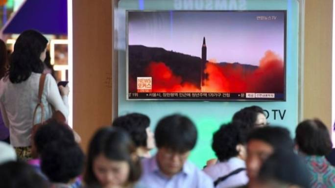People watch a television broadcasting a news report on North Korea firing a missile that flew over Japan's northern Hokkaido far out into the Pacific Ocean (Photo: the Guardian)