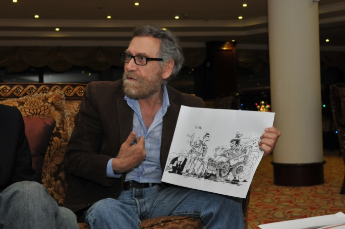 Ali Ferzat holding one of the cartoons which irked the regime, with Syrian president Assad dipicted hitching a lift from Libyan dictator Muammar Gaddafi