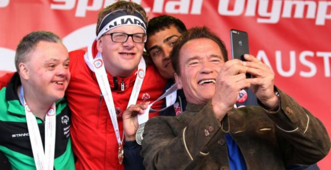Arnold Schwarzenegger taking a selfie with some of the athletes from the 2017 Winter special Olympics