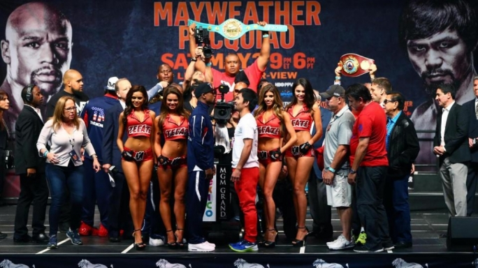 Floyd Mayweather (left) stares at Manny Pacquiao during the weigh-ins for their upcoming boxing fight at MGM Grand Garden Arena
