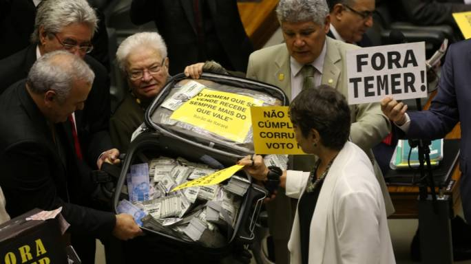 Opposition deputies hold a suitcase with fake money before the vote in congress (Adriano Machado for Reuters)