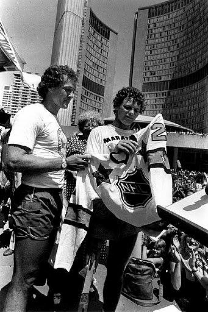 Canadian hockey legend Darryl Sittler presents Terry Fox with the Canadian All-Star hockey team shirt