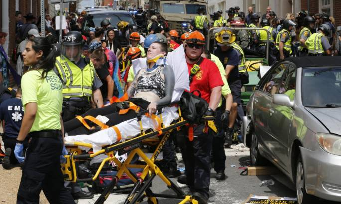 Rescue personnel help injured people after a car ran into a large group