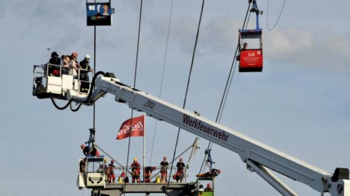 German fire crews evacuate trapped passengers from suspended cable cars that run over the river Rhine after a gondola ran into a support pillar in Cologne, Germany, 30 July 2017Image copyrightEPA Image caption Fire crews use a crane to evacuate trapped passengers as high as 40m in the air