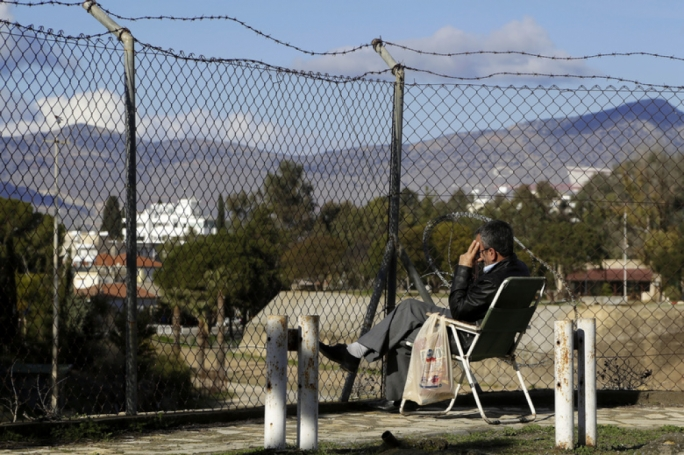 A man sits in front of the fence that divides the Greek and Turkish Cypriots areas