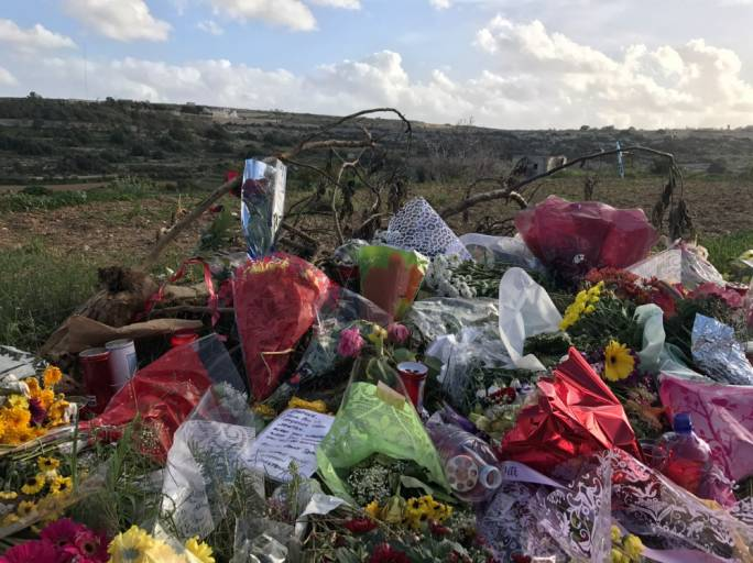 Flowers and candles left by mourners near the bomb site where Daphne Caruana Galizia was murdered