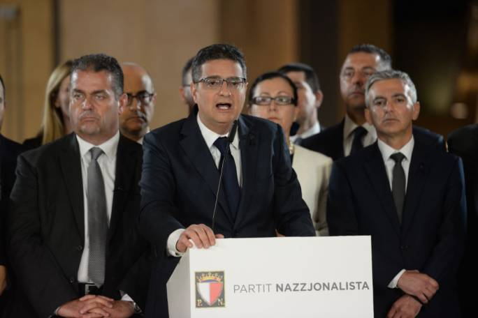 Behind you! Adrian Delia addresses the press after his Budget reply on Tuesday night. His predecessor Simon Busuttil (right) was sure to make his presence felt