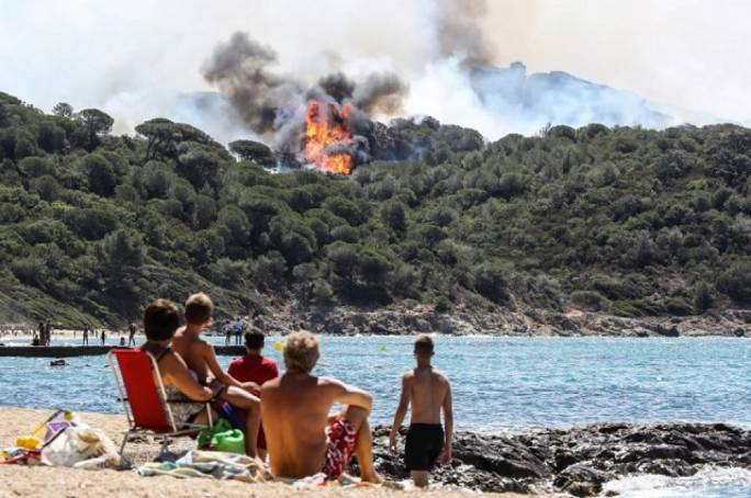 People on beach look at a forest fire in La Croix-Valmer, near Saint-Tropez
