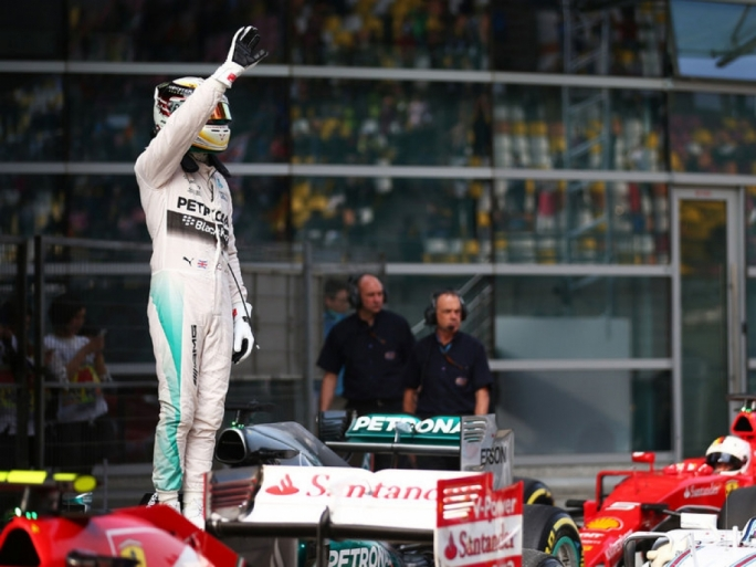 Lewis Hamilton waves to the fans after securing pole position