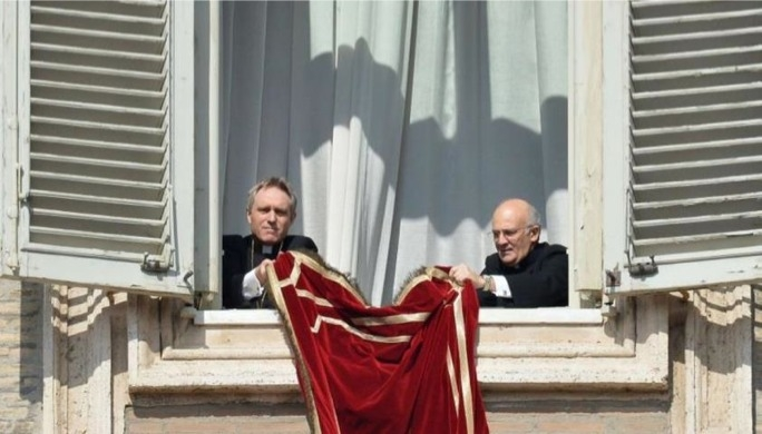 Mgr Alfred Xuereb (right) unfolding the Papal drape on the Pontiff's window before Pope Benedict's final Angelus last month.