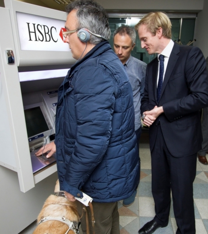 Visually impaired HSBC customer Joseph Stafrace, accompanied by his guide dog, trying his hand on the bank's Talking ATM as Gordon Gilford and Andrew Beane look on