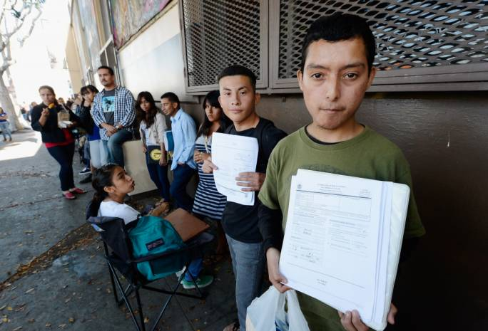Young immigrants holding up their applications to Daca. Source: KQED