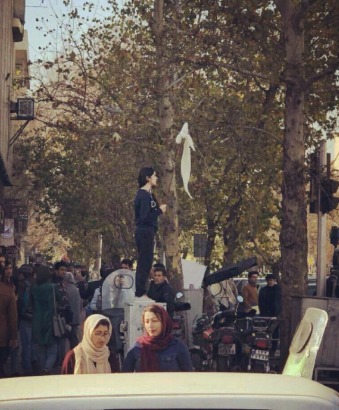 A protester in Tehran hoists her mandatory hijab on a stick