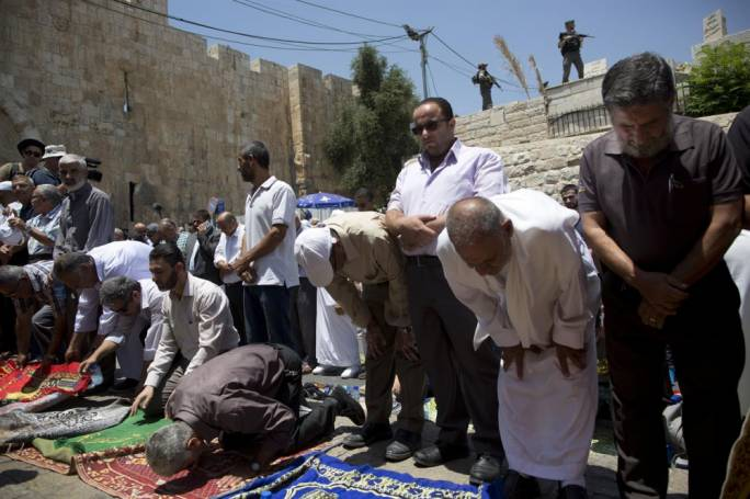Palestinian Muslims pray outside the Lion's Gate following an appeal from clerics to pray in the streets instead of the Al Aqsa Mosque compound