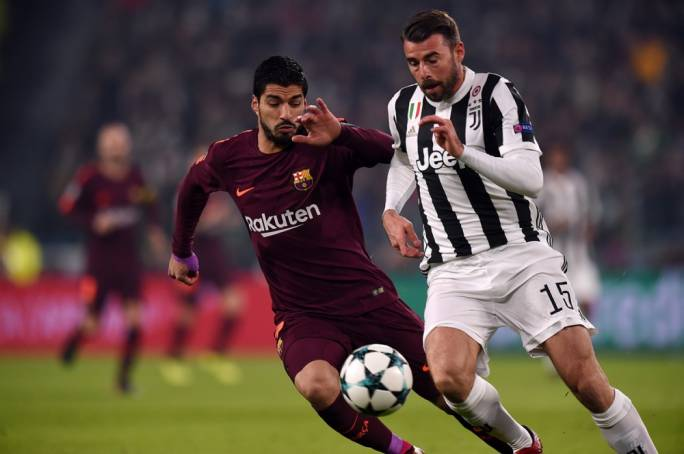 Andrea Barzagli (Juventus) and Luis Suarez (Barcelona) in action