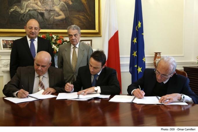 Caritas director Leonid McKay (centre) signing the public social partnership deal