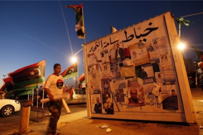 A Libyan man walks by campaign posters for tomorrow's General National Congress election