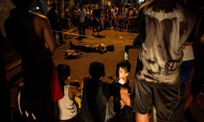 Residents surround the body of an alleged drug user killed in Manila