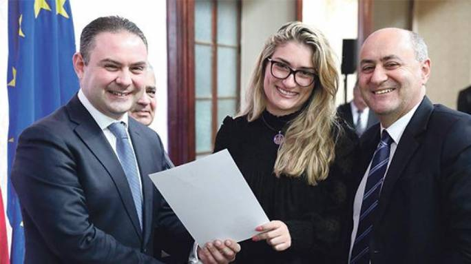 Justice Minister Owen Bonnici handing Martina Herrera her warrant last February. Her father, Environment Minister Josè Herrera stands at right. Photo: Facebook
