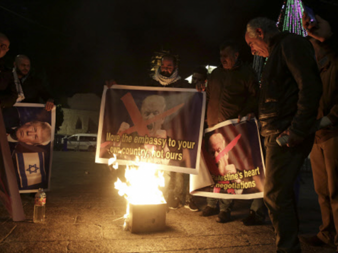 Palestinian burn a poster of Donald Trump during a protest in Bethlehem, West Bank on 6 December, 2017.
