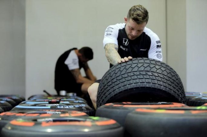 McLaren Formula One crew prepare tyres in the paddock ahead of the Singapore F1 Grand Prix September 17, 2015