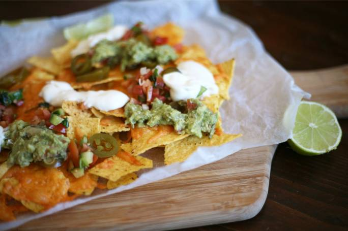 Cheesy nachos with guac, tomato salsa and sour cream
