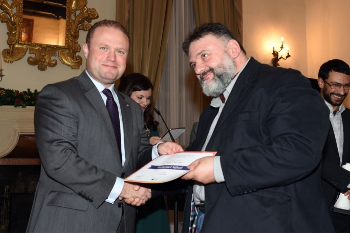 Prime Minister Joseph Muscat hands novelist Immanuel Mifsud his winning certificate at this year's edition of the National Book Prize