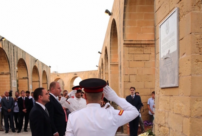Justice minister Owen Bonnici (left) salutes the memory of the 13 sailors who died aboard the Kujawiak