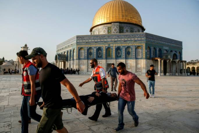 Palestinian paramedics carry an injured woman on a stretcher past the Dome of the Rock, after clashes broke out inside the Al-Aqsa mosque compound in Jerusalem's Old City
