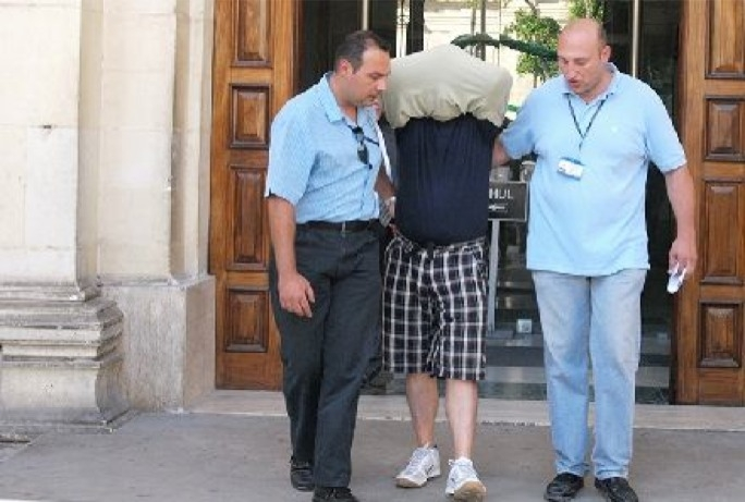 File photo from 2010: Vince Muscat 'il-Kohhu' is escorted from court after being charged with involvement in the 2010 HSBC heist