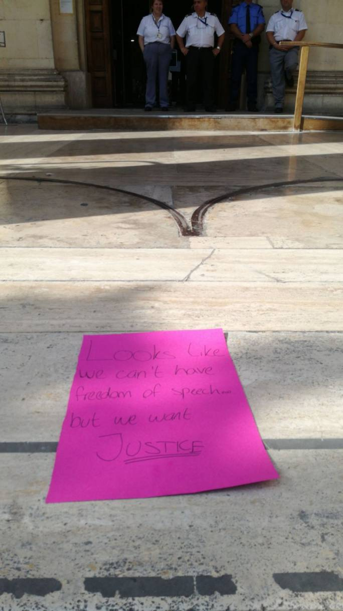 A placard left by protestors in front of the law courts