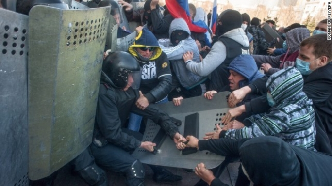 Pro-Russian protesters clash with police as they try to occupy a regional administration building in Donetsk