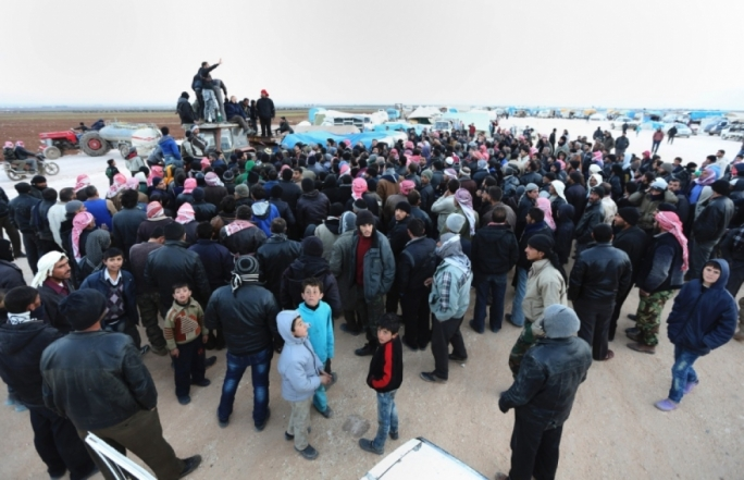 Syrians gather at the Bab al-Salam border gate with Turkey, in Syria
