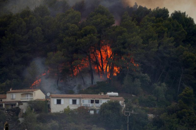 Flames from a burning wildfire are see near homes in Carros, near Nice, France
