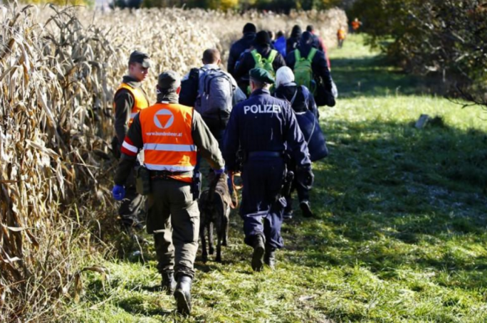 Members of the Austrian army and police escort a group of migrants arriving from Slovenia at the border crossing in Spielfeld, Austria, 20 October 2015