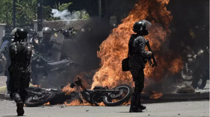 Armed police stand guard after a bomb attack injured seven of their colleagues in Caracas on Sunday