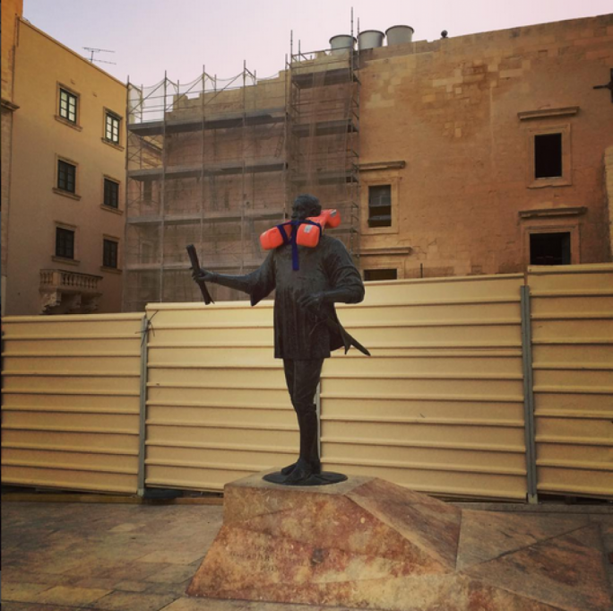 Ten life jackets shrouded Valletta statues in an effort to bring awareness to migrants dying along the Libyan coast